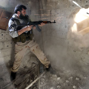 A Free Syrian Army fighter fires through an opening in a wall in the Mleha suburb of Damascus. (Reuters file)