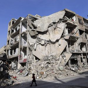 A girl walks past buildings destroyed by Syrian air force strikes in the Duma neighborhood of Damascus. (Reuters file)