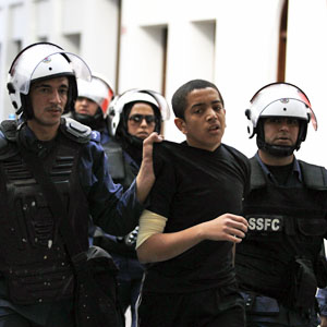 Riot police arrest a protester during an anti-government rally in Bahrain's capital, Manama, December 17, 2012.