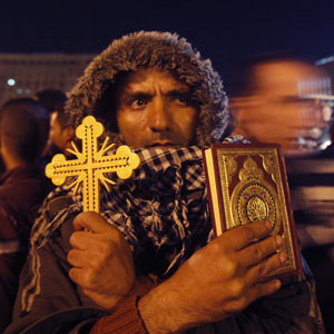 An anti-government protester holds a Christian Cross and a copy of the Quran at a rally in Cairo's Tahrir Square December 12, 2012. (Reuters)