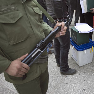 An Iranian police officer guards a ballot box during Iran's parliamentary election in Tehran March 2, 2012. (Reuters)