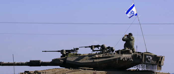 Israeli soldier looks through binoculars atop tank near Kissufim