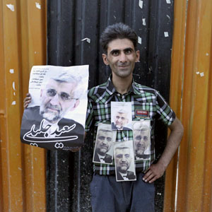 An Iranian man holds posters of presidential candidate Saeed Jalili, who is also Iran's top nuclear negotiator, in a street campaign in Tehran June 6, 2013.