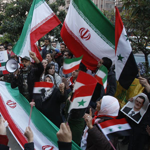 Assad-supporters shout slogans and wave Iranian and Syrian flags during a rally in front the Iranian embassy to thank Tehran for its support of the Syrian regime, in Damascus, Syria, November 24, 2011. (AP)