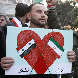 "An Assad supporter holds a placard showing the Iranian and Syrian flags with Arabic words reading: ""Thanks Iran,"" during a rally in front the Iranian embassy to thank Tehran for its support of the Syrian regime, in Damascus, Syria, November 24, 2011. (AP)"