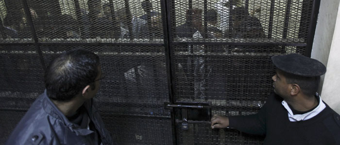 NGO workers are seen kept under guard in a cage during the opening of their trial in Cairo March 8, 2012. (Reuters)