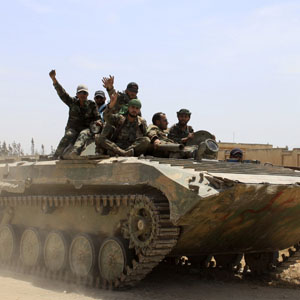 Syrian government soldiers gesture atop a tank near Qusair June 7, 2013. (Reuters)