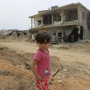 A child is seen in front of a damaged house in Qusair June 8, 2013.