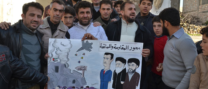 Syrians hold a placard lampooning (L-R) Syria's President Bashar al-Assad, Iran's Supreme Leader Ayatollah Ali Khamenei and Hezbollah leader Hassan Nasrallah in Kafranbel near Idlib, Syria. (Reuters file)