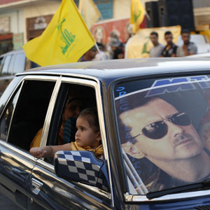 A poster of Syria's President Bashar al-Assad is seen displayed on a car's windshield as Hezbollah supporters celebrate the fall of Qusair, in the Lebanese Shi'ite town of Hermel June 5, 2013. (Reuters)