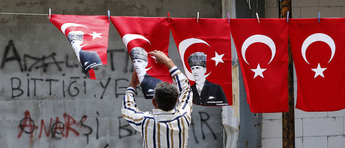 A man displays Turkey's national flags and flags printed with portraits of Mustafa Kemal Ataturk in Ankara