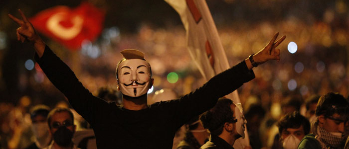 An anti-government protester, wearing a Guy Fawkes mask, makes V-signs during clashes in Ankara (Reuters).