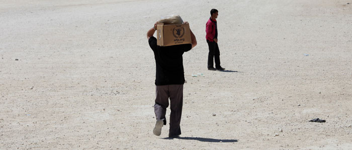 A Syrian refugee carries his belongings a refugee camp in Mafraq, Jordan, April 25, 2013. (Reuters)