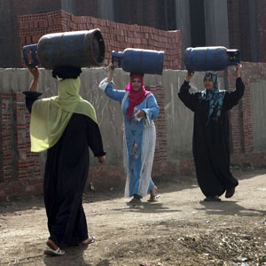 Women carry gas cylinders to be refilled on the outskirts of Cairo, April 1, 2013. (Reuters)