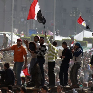 Protesters wave flags and shout slogans near an army tank during an anti-Mubarak rally in Cairo's Tahrir Square Cairo February 8, 2011. (Reuters)