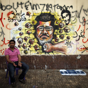 A man sits next to anti-Morsi graffiti painted on a wall of the Presidential Palace in Cairo July 2, 2013. (Reuters)