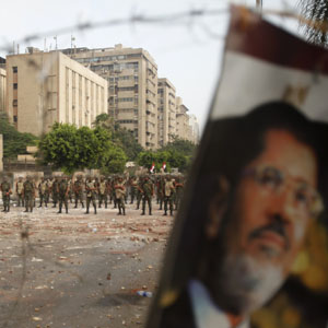 A Morsi poster mounted on a barbed wire barricade is seen against the backdrop of soldiers near Republican Guard headquarters in Cairo July 9, 2013. (Reuters)