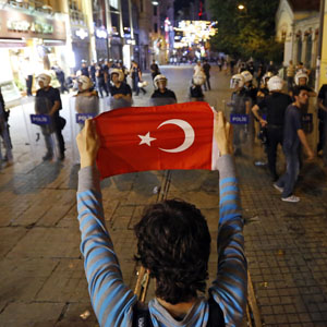 A protester holds the Turkish flag in front of a riot police line in Istanbul June 22, 2013. (Reuters)