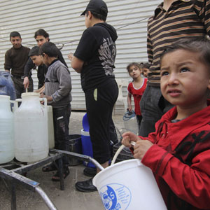Residents and children wait to collect water in Aleppo, April 2, 2013. (Reuters)