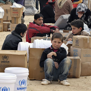 Syrian refugees wait to receive aid at Al-Zaatri refugee camp in the Jordanian city of Mafraq, near the border with Syria, January 25, 2013. (Reuters)