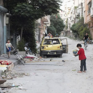Children play along a street in Homs June 20, 2013. (Reuters)