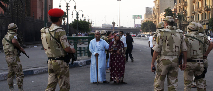 Pedestrians look as the Egyptian army soldiers divert traffic away from the Egyptian museum in Cairo