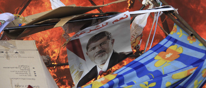 "A poster of deposed president Mohamed Morsi  reads ""Yes to legitimacy."" at a protest camp of his supporters cleared by security forces in Cairo August 14, 2013. (Reuters)"