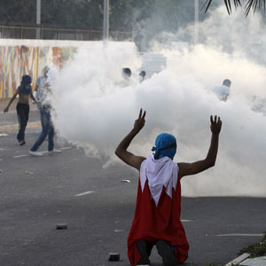 A protester wearing Bahraini flag gestures towards riot police using tear gas during clashes in the village of Bani Jamra, west of Manama, May 24, 2013.