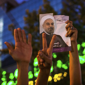 Supporters of Hassan Rohani hold a picture of him as they celebrate his victory in Iran's presidential election in Tehran in this June 15, 2013, file photo. (Reuters)
