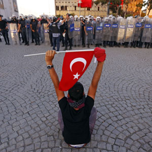 A protester holds a Turkish flag as he sits in front of riot police at Taksim Square in Istanbul June 22, 2013. (Reuters)