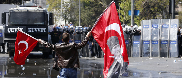 A protester waves Turkish flags, one bearing a portrait of Mustafa Kemal Ataturk, the founder of modern Turkey, as he tries to break through police barricades near Istanbul's main square May 1, 2013. (Reuters)