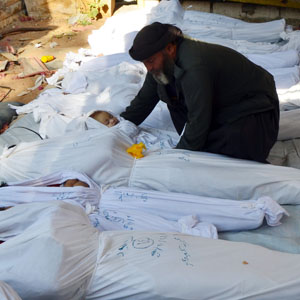 A man holds the body of a dead child among bodies of purported victims of a nerve gas attack, in the Duma neighborhood of Damascus August 21, 2013. (Reuters)