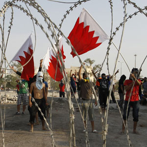 Protesters hold up Bahraini flags in front of a barb wire barricade set up by riot police in the village of Shakhoora, west of Manama, August 14, 2013. (Reuters)