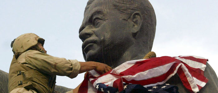 A U.S. Marine prepares to cover the face of a statue of Iraqi President Saddam Hussein with a U.S. flag in Baghdad in this April 9, 2003, file photo (Reuters).