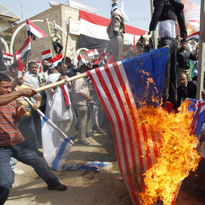 Supporters of Shi'ite cleric Moqtada al-Sadr burn a U.S. flag during a rally in Najaf in this April 9, 2010, file photo. Hanging in the background are effigies of U.S. officials. (Reuters)