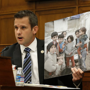 U.S. Representative Adam Kinzinger holds a picture of Syrian children as he addresses U.S. Secretary of State John Kerry during congressional hearings on U.S. military action against Syria, in Washington, D.C., September 3, 2013. (Reuters)