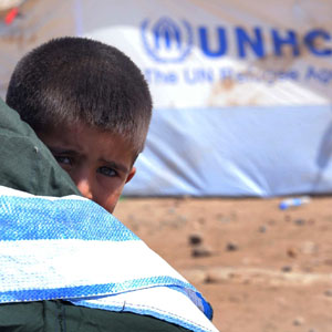 A Syrian refugee boy peeks from behind a tent at the Quru Gusik refugee camp on the outskirts of Arbil in Iraq's Kurdistan region, August 23, 2013. (Reuters)