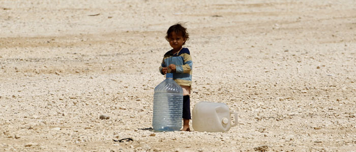 A young Syrian refugee stands beside water containers at Zaatari refugee camp in Jordan September 1, 2013 (Reuters).