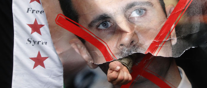 A demonstrator punches through a poster of Syria's President Bashar al-Assad during a protest outside the Syrian Embassy in London (Reuters file).