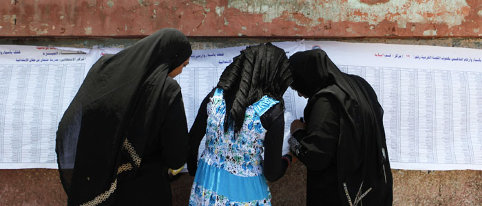 Women check for names before casting their votes during the second day of voting in Egypt's presidential election
