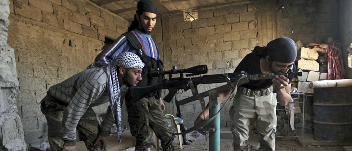 Free Syrian Army fighters calibrate a sniper rifle in Deir al-Zor