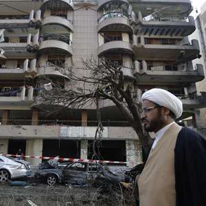 A Shi'ite cleric passes in front of a damaged building, at the scene where explosions struck, a day before, near the Iranian embassy in Beirut, November 20, 2013. (AP)