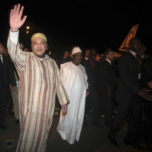 King Mohammed (L) of Morocco waves as he is welcomed by Mali's President Ibrahim Boubacar Keita (in white) at the Bamako-Senou International Airport September 18, 2013. (Reuters)