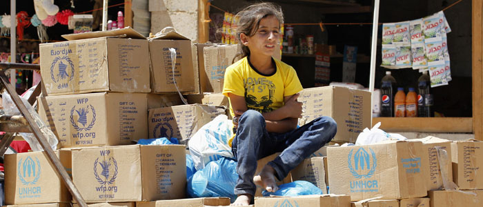 FILE - A Syrian refugee girl sits atop humanitarian aid boxes at Za'atri camp in Jordan. (Reuters)