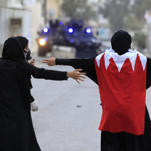Two female anti-government protesters, one draped in a Bahraini flag, confront riot police vehicles during clashes in Sitra March 24, 2012. (Reuters)