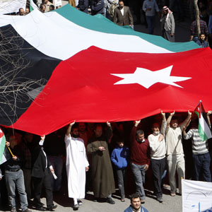 Anti-government protesters carry a Jordanian flag during a rally in Amman March 18, 2011. (Reuters)