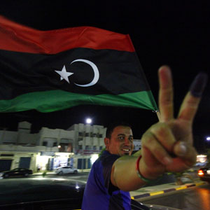 A man, with an ink-stained finger, flashes the victory sign as he celebrates holding a Libyan flag at the end of voting day in Sirte July 7, 2012. (Reuters)