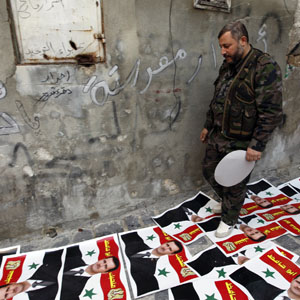 A Free Syrian Army fighter walks on posters depicting Syria's President Bashar al-Assad spread on a street in Aleppo November 16, 2012. (Reuters)