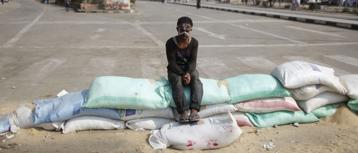 A protester, with his forehead painted with the colors of the Egyptian flag, sits on sand bags securing the entrance of Cairo's Tahrir Square July 9, 2013. (Reuters)