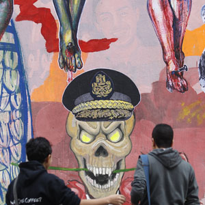Youth talk in front of wall with graffiti opposing the Egyptian military in downtown Cairo December 5, 2013. (Reuters)